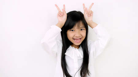 Asian child girl is smiling cute and uses her finger to act like a rabbit on a white background.