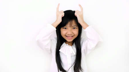 Asian child girl is smiling cute and uses her left index finger and right index finger to act like a bull horn on a white background.