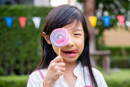 Asian child girl happily holds a rainbow meringue in her hand. Stock Photo