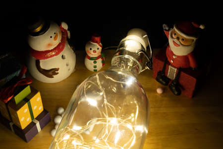 Home decoration with lights in glass bottles and snowman dolls, gift boxes and Santa Claus to welcome the season of joy, merry, Christmas and happy new year 2021.