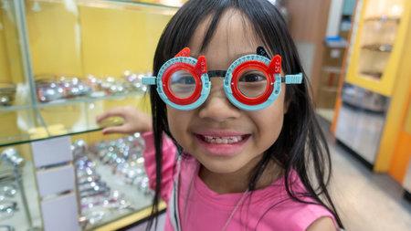 Asian child girl in an eyeglass shop wearing measuring glasses, pediatric refractive disorder Stock Photo