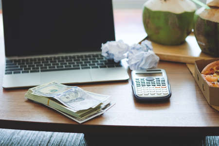 Dollar bills on a wooden table with a notebook computer with a calculator
