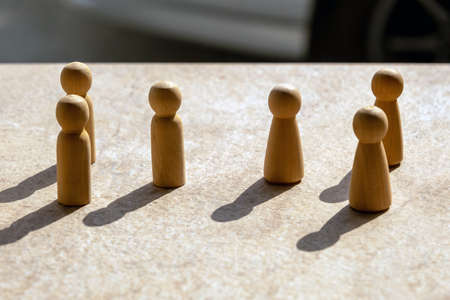 Wooden models simulating men and women, or a division of 3 people each talking or negotiating business. Stock Photo