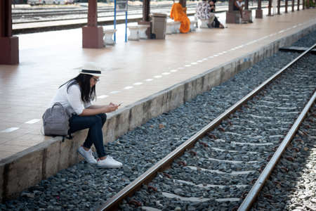 Asian woman tourist with hat is wearing a white and gray backpack uses a smartphone while waiting for a train at a station.
