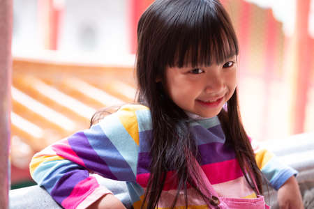 Asian child girl wearing jumpsuit jeans and T-shirts of many colors sitting on the balcony and smile happily.
