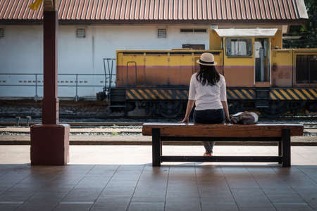 The back of the Asian woman tourist with hat is wearing a white and gray backpack while waiting for the train at the station