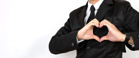 A business man wearing a suit uses a hand at the heart symbol on a white background, care concept or care away from heart disease.