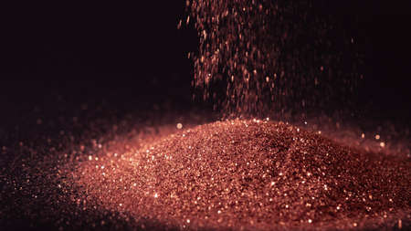 Glittering pink gold powder sprinkled on pile on black background