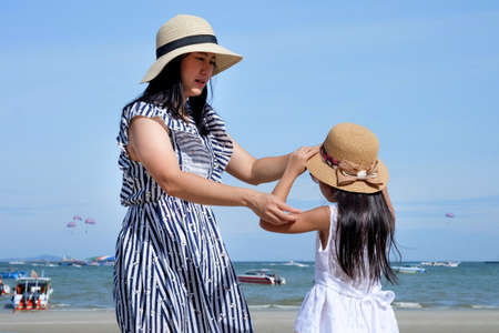 Mom wearing a hat for her daughter on the beach on vacation, Asian family