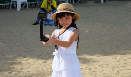 Asian child girls tourists are using action cam to record events while she is traveling to go to social media.