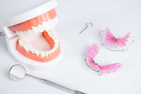 Removable orthodontic or orthodontic devices for children with crooked teeth, model teeth and dental mirror on white background.