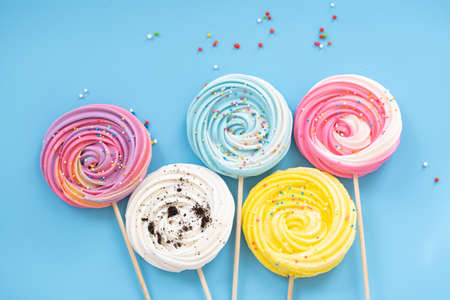 Lollipop Meringue Dessert Sprinkled with blue bow on a blue background with colorful toppings.