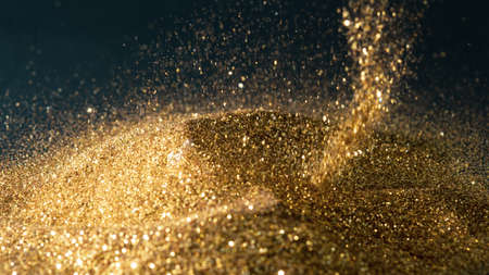 Glittering gold powder sprinkled on a pile of gold on a black background
