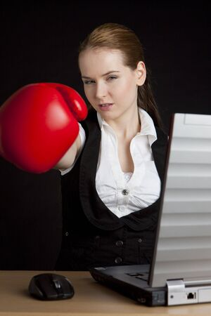 businesswoman  with boxing gloves at notebook photo