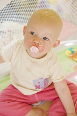 portrait of toddler with pacifier sitting in cot photo
