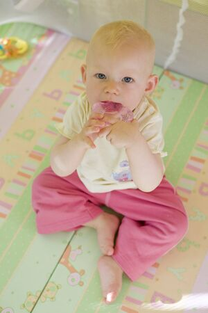 toddler with teether sitting in cot photo