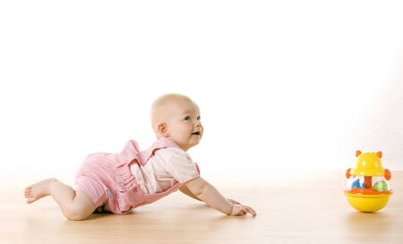 crawling: baby girl crawling towards a toy on the floor
