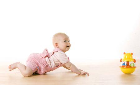baby crawling: ni�a arrastr�ndose hacia un juguete en el piso Foto de archivo