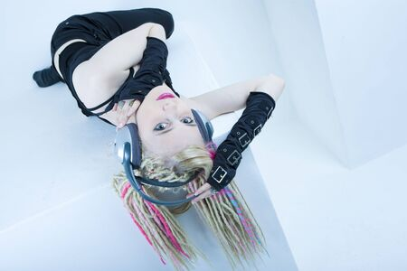 portrait of lying young woman with dreadlocks with headphones photo