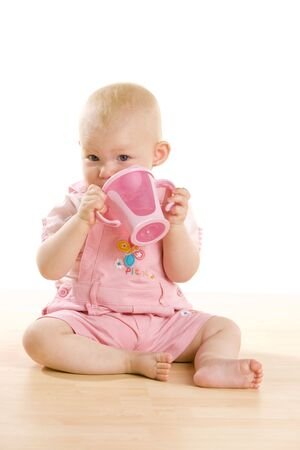 baby girl with a mug sitting on the floor photo
