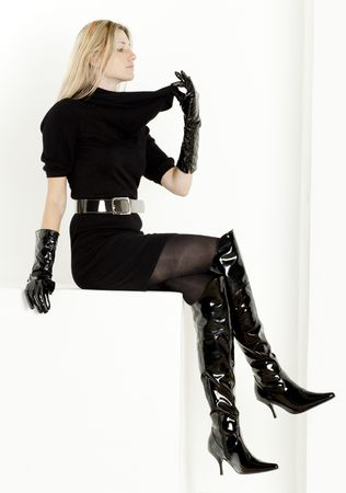 sitting woman wearing black dress and fashionable boots photo