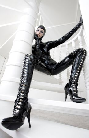 woman in latex sitting on the stairs photo