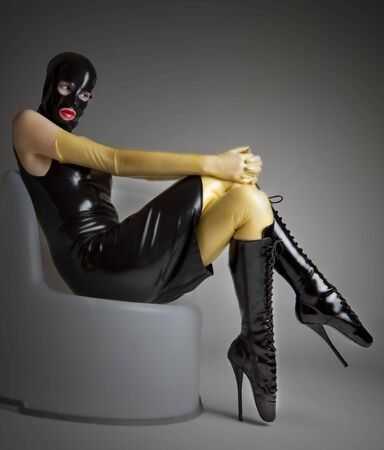 woman in latex sitting on the chair photo
