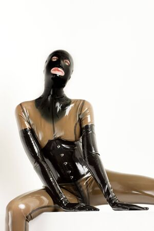 extravagancy: portrait of sitting woman wearing latex clothes