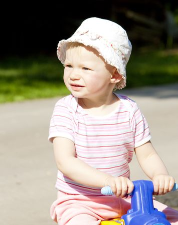 portrait of little girl on toy motorcycle photo