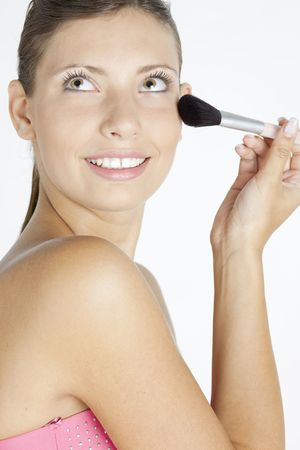 portrait of young woman putting on face powder photo