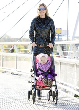 woman with toddler sitting in pram on walk photo