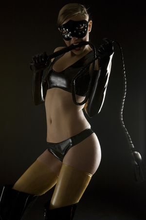 skintight: woman wearing latex clothes with whip Stock Photo