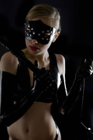 portrait of woman wearing latex clothes with whip photo