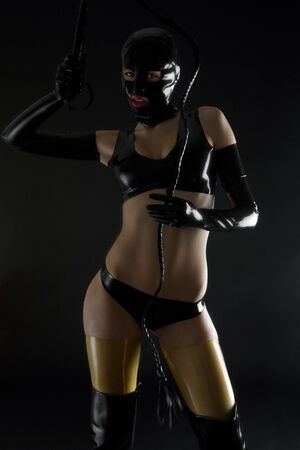 domina: woman wearing latex clothes with whip Stock Photo