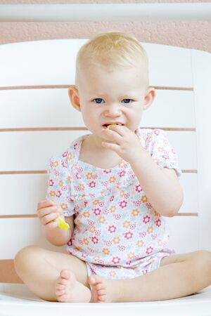sitting toddler eating an apple photo