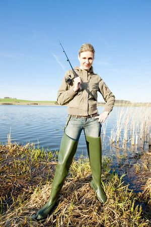 resting rod fishing: woman fishing at a pond