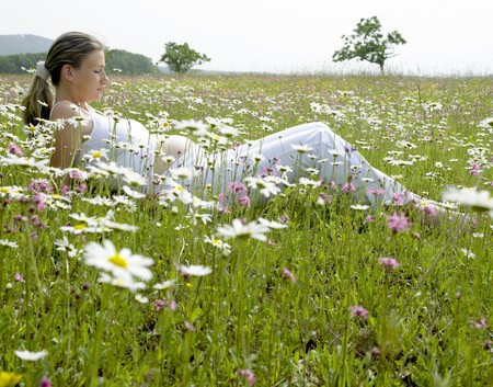 woman lying down: pregnat woman on meadow