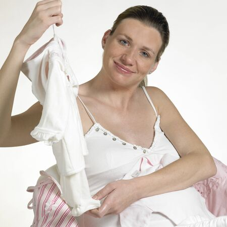 mammas: pregnat woman with clothes for babies Stock Photo