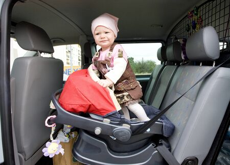 little girl standing in car seat photo