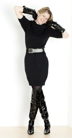 long haired: standing woman wearing black dress and fashionable boots