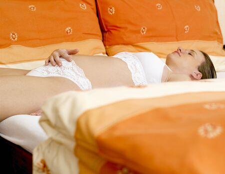 pregnant underwear: mujer pregnat en cama  Foto de archivo