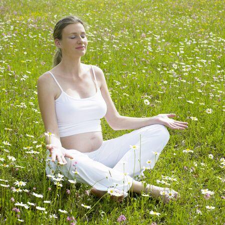 mammas: pregnat woman sitting on meadow