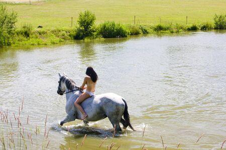equestrian on horseback riding through water photo