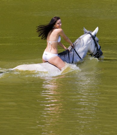 free riding: equestrian on horseback riding through water