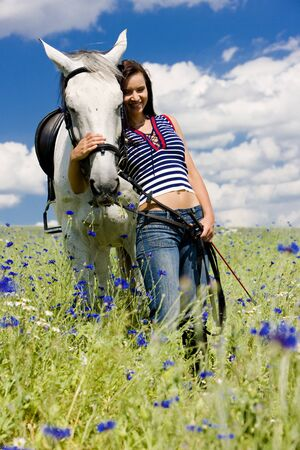 free riding: equestrian with a horse on meadow Stock Photo
