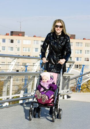 woman with toddler sitting in pram on walk photo