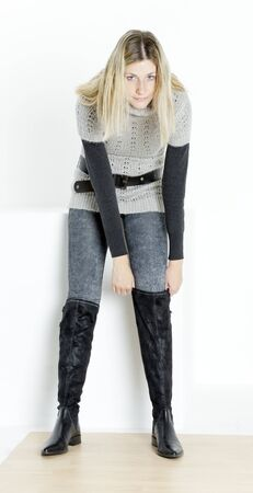 pullovers: standing woman putting on fashionable boots