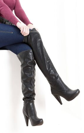 detail of sitting woman wearing fashionable boots photo