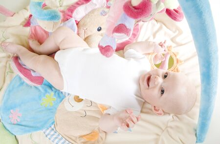 baby girl lying down on playing mat photo