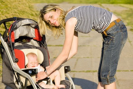 woman with baby sitting in pram Stock Photo - 7502728